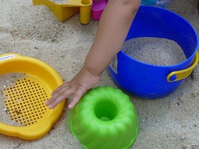 Kind spielend im Sand