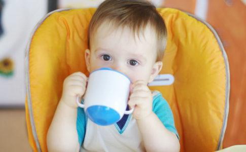 Kleinkind, das aus einem Trinklernbecher trinkt
