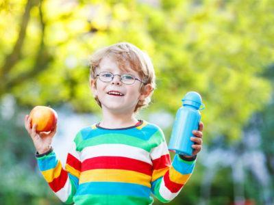 Kind hält Apfel und Trinkflasche in den Händen