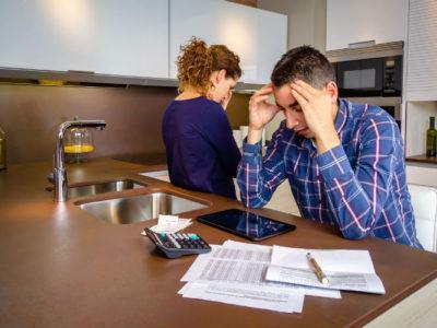 Arbeitslosigkeit - verzweifeltes junges Paar in Küche