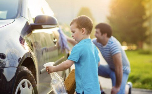 Kind wäscht Auto zusammen mit Vater