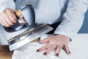 Frau hält Bügeleisen über Hand auf Bügelbrett