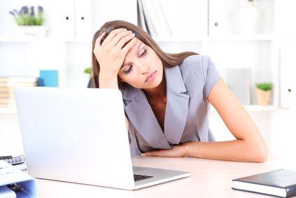 Eine junge Geschäftsfrau sitzt gestresst an Ihrem Schreibtisch.