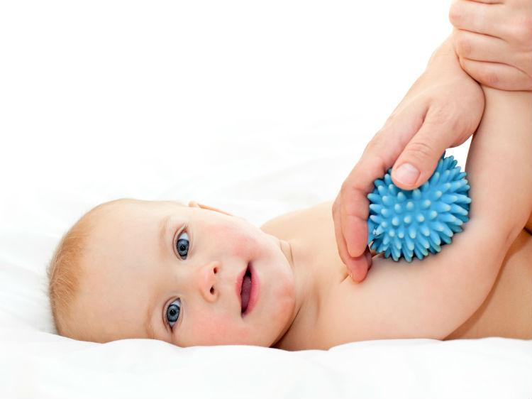 Baby Massage mit einem weichem Massageball