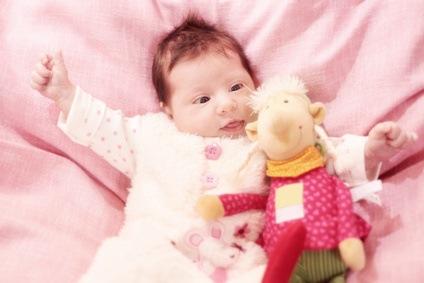 Ein kleines Baby liegt mit einem Kuscheltier auf einer Decke.