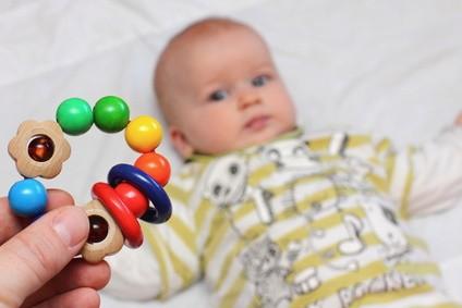 Ein Baby erwartet ein Babyspielzeug.