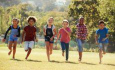 Kinder laufen barfuß und lachend über eine Wiese