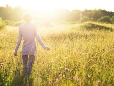 Frau geht in der Sonne spazieren