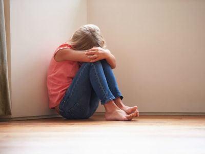Ein junges Mädchen, das traurig am Boden sitzt