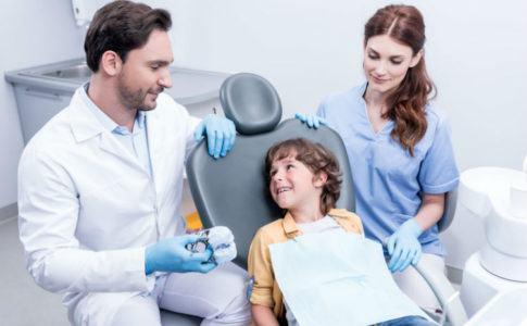 Kleiner Junge beim Kieferorthophaeden, dem etwas vom Arzt erklärt wird