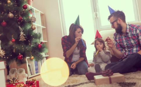 Eltern, die mit ihrem Kind gemeinsam Silvester im Wohnzimmer feiern