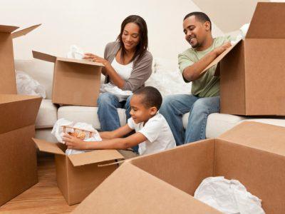 dreikpfige-familie-packt-umzugskartons-aus-in-neuer-wohnung