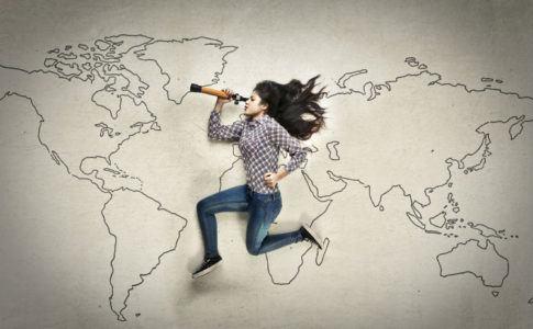 Schülerin schaut durch ein Fernglas in das Schuljahr im Ausland