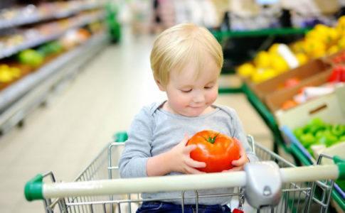 Kleines Kind, das im Einkaufswagen sitzt und eine Tomate in den Haenden haelt
