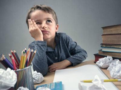 Kind sitzt am Schreibtisch zwischen Büchern und zusammengeknülltem Papier und kämpft mit Hausaufgaben