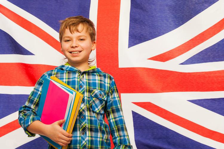 Englisch lernen - Junge mit Lernbüchern vor Großbritannien Flagge