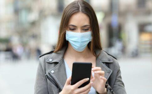 Frau mit Maske benutzt Handy