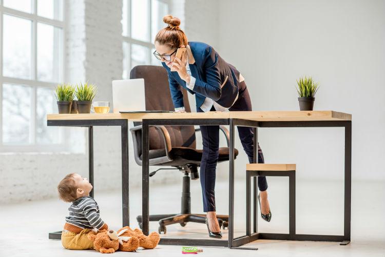 Mutter arbeitet während sie auf ihr Kind aufpasst