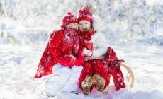 Zwei Kinder sitzen auf dem Schlitten und Lachen im Winter