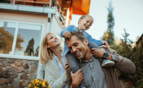 Familie steht glücklich vor ihrem Haus