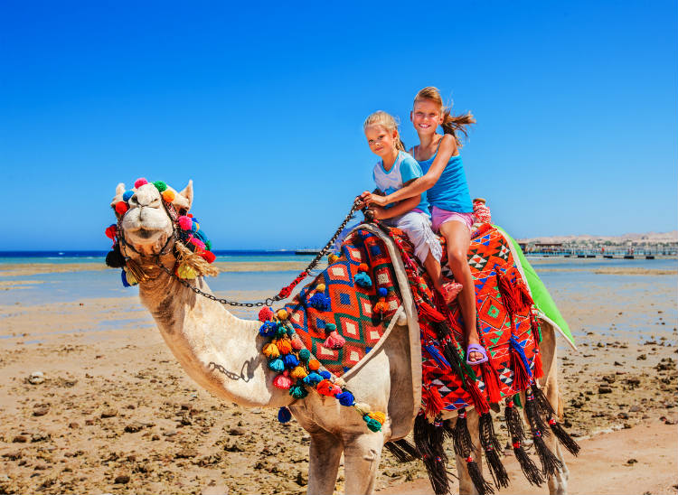 Zwei Mädchen reiten auf einem Kamel am Strand