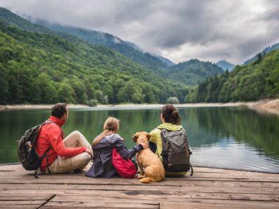 Familie mit Hund macht eine Wanderpause am See