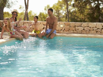 Vierköpfige Familie sitzt lachend am Poolrand und spritzt sich mit Wasser nass