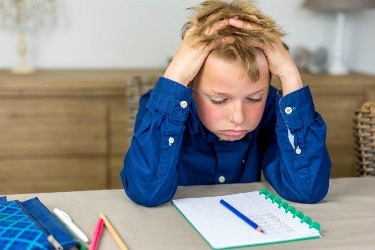 Junge sitzt an Hausaufgaben