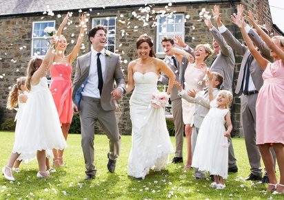 Gäste werfen Konfetti auf das Hochzeitspaar