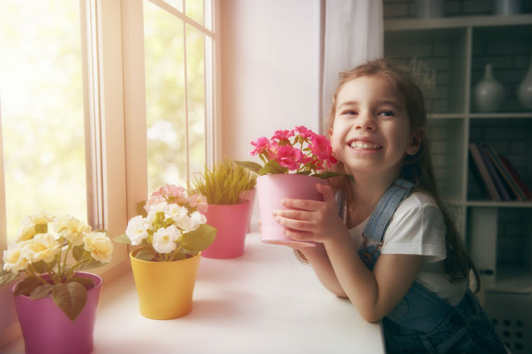 Frühling- Mädchen mit Blumen am Fenster