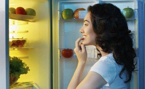 Frau steht vor dem Kühlschrank und überlegt was sie essen kann