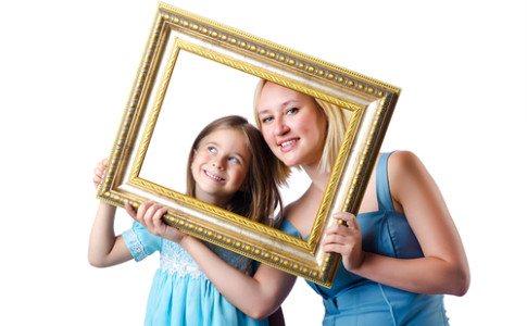 Geschwister posieren hinter einem Bilderrahmen.