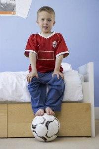 Kleiner Junge mit einem Fußball unter seinen Füßen.