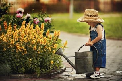 Ein Kind beim Blumengießen im kindgerechten Garten.