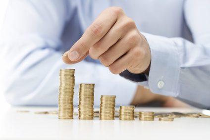 Ein Mann stapelt Münzen zu Münztürmen in unterschiedlicher Größe.