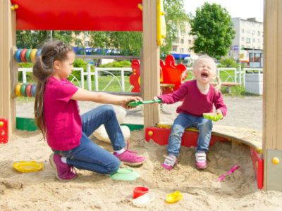 Geschwister die sich auf einem Spielplatz um eine Schaufel streiten