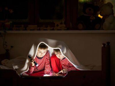 Geschwister lesen in einem gemeinsamen Zimmer unter der Decke