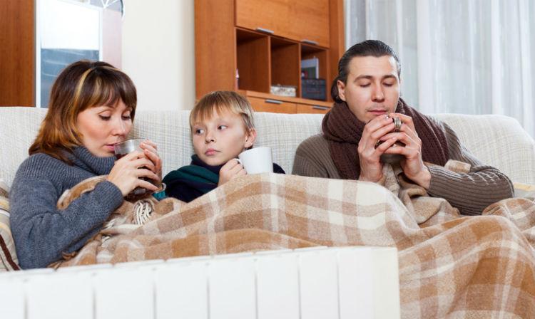 Eine Familie, die erkältet zusammen auf dem Sofa liegt und Tee trinkt
