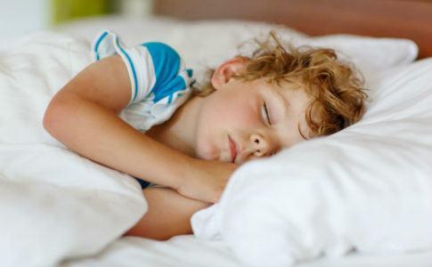Kleiner Junge liegt im Bett und schläft