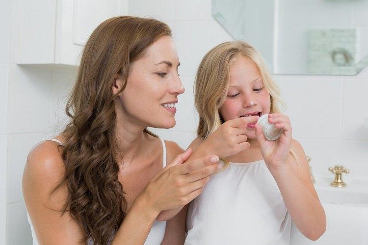 Mutter und Tochter machen gemeinsam Hautpflege im Winter