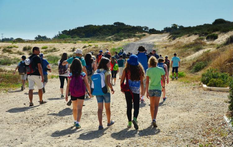 Kinder auf einer Klassenfahrt auf dem Weg zum Strand