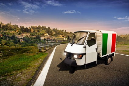 Ein kleiner italienischer Transporter steht auf einer verlassenen Straße vor herrlicher Landschaft.