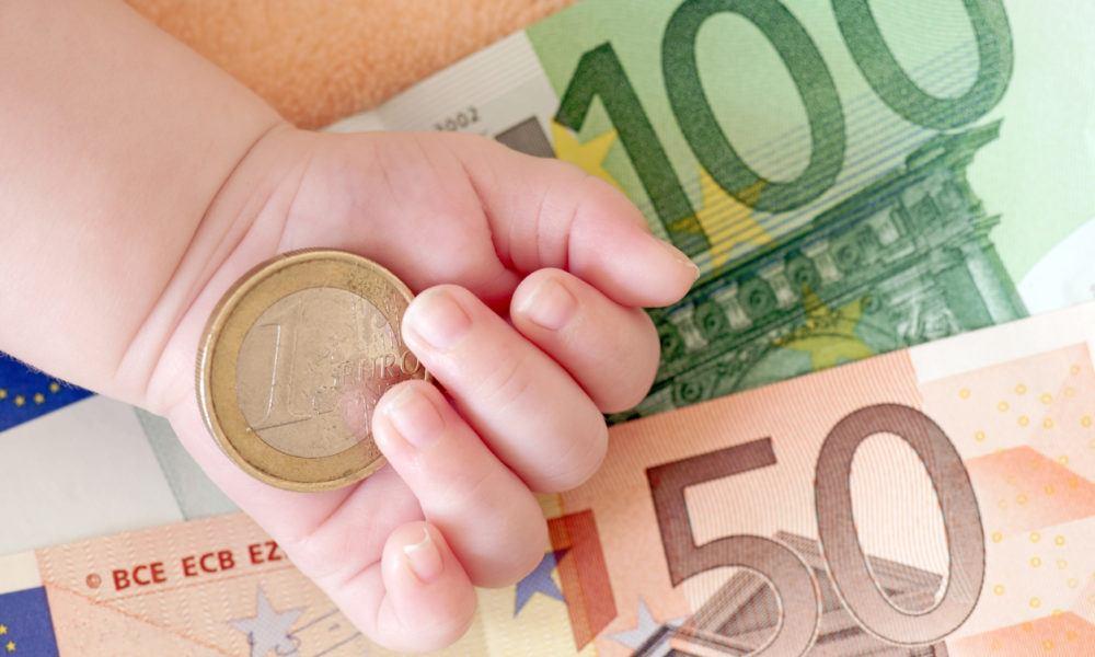 Euronoten und Geldstück mit einer Babyhand im Bild