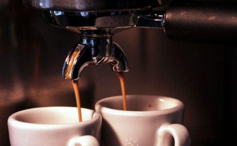 zwei Tassen unter laufender Kaffeemaschine
