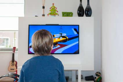 Ein Kind sitzt im Wohnzimmer vor dem Fernseher.