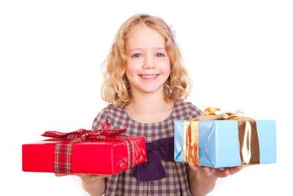 Ein lachendes Kind mit zwei Geschenken in der Hand.