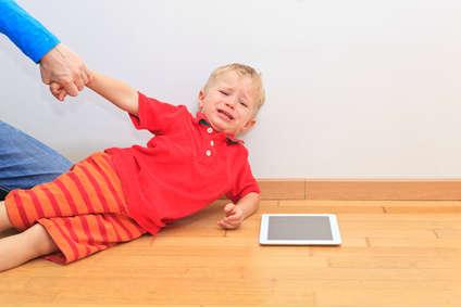 Ein Kind möchte nicht vom Tablet weg und weint.