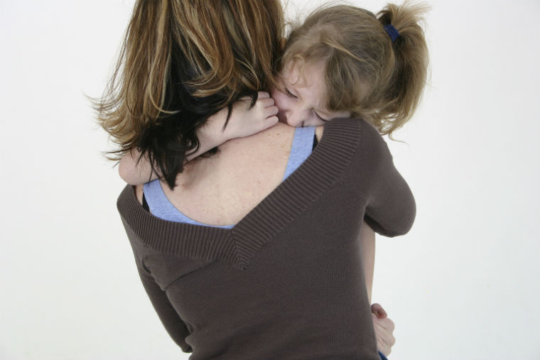 Kind klammert sich um Mama