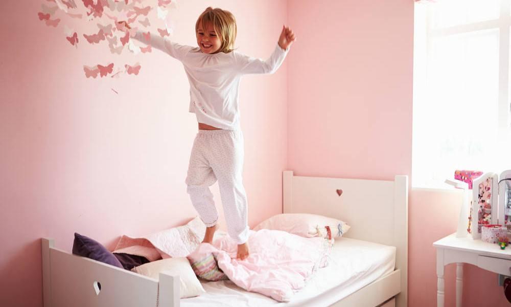 Mädchen springt auf ihrem Bett