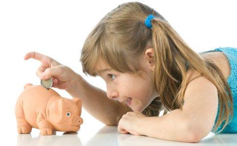 Kind steckt Münze ins Sparschwein